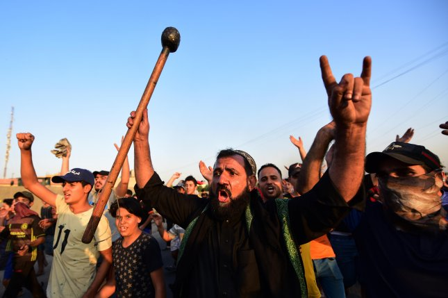 Iraqis protest in east Baghdad on Wednesday. Photo by Murtaja Lateef/EPA-EFE