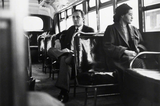 Rosa Parks sits up front of a Montgomery, Ala. bus, posed with UPI reporter Nicholas Chriss in on December 21,1956, one year after she refused to give up her seat to a white man and was arrested. Photo by UPI