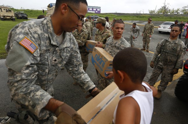 The U.S. Army has signed a contract with the Louis Berger Group to support temporary power to parts of Puerto Rico and the Virgin Islands that remain without electricity since the islands were slammed by Hurricane Maria in September. Picture, members of the Army deliver supplies to people affected by the storm in Las Piedras, Puerto Rico. Photo by Thais Llorca/EPA-EFE