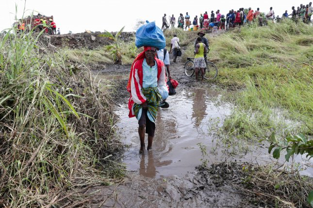 People walk by the only access route possible in the area of Joao Segredo where the major road was damaged after the passage of Cyclone Idai in the province of Sofala, Mozambique, on Saturday. Photo by Tiago Petinga/EPA-EFE