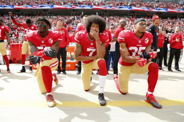 Former San Francisco 49ers quarterback Colin Kaepernick (C), outside linebacker Eli Harold (L) and free safety Eric Reid (R) take a knee during the U.S. national anthem in October 2016. Kaepernick will have a private workout on Saturday. File Photo by John Mabanglo/EPA