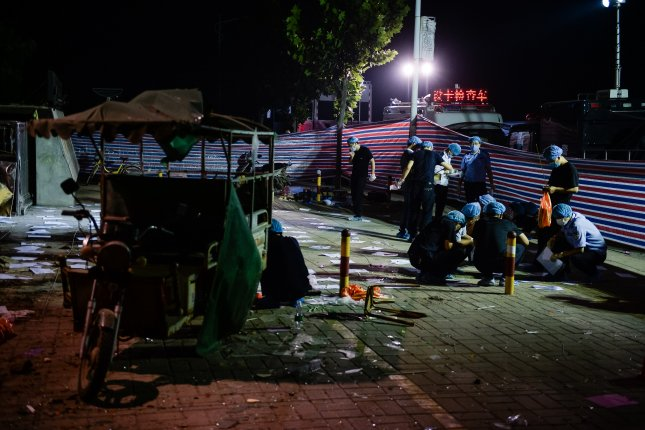 Chinese forensic experts work at the site of an explosion near a kindergarten in Fengxian county, in eastern China's Jiangsu province on Friday. Police said the explosion was caused by a homemade bomb planted outside the school. Photo by Li Xiang/Xinhua/EPA