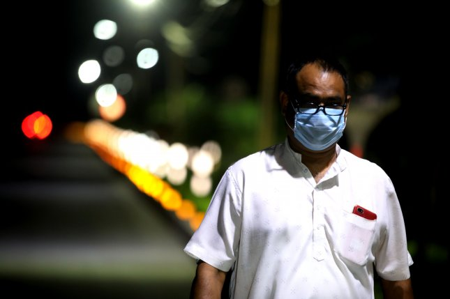 An Indian man wears a protective face mask while walking on a deserted street in Bhopal, India, on Sunday. Photo by Sanjeev Gupta/EPA-EFE