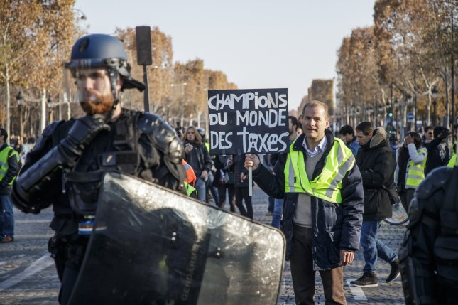 A man wearing a yellow vest holds a banner reading World Champions of the Taxes during a demonstration in Paris as part of a nationwide protest that started Saturday, November 17, 2018. Photo by Cristophe Petit Tesson/EPA-EFE EPA-EFE