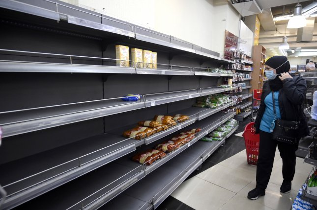 A customer walks past an sparsely stocked shelf in a supermarket in Beirut, Lebanon, on March 24. Photo by Wael Hamzeh/EPA-EFE