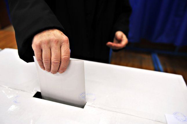 A man drops his vote into a ballot box on election day. Photo by roibu/UPI via Shutterstock