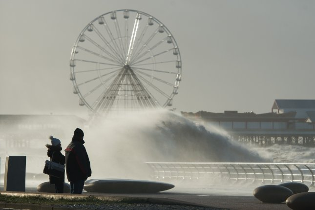 Members of the public look at waves crashing against the breakwater as storm Eleanor hits the coastline in Blackpool, Britain. Photo by Peter Powell/EPA