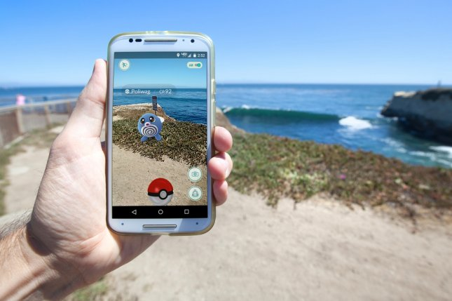 A man plays Pokemon Go on a California beach. Two men fell from a cliff in Encinitas, Calif., while playing the smartphone game. Photo by Matthew Corley/Shutterstock.com