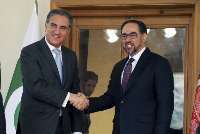Pakistan's Minister of Foreign Affairs Shah Mehmood Qureshi (L) and Afghanistan's Foreign Minister Salahuddin Rabbani shake hands Saturday after a trilateral anti-terrorism conference that included China in Kabul, Afghanistan. Photo by Jawad Jalali/EPA