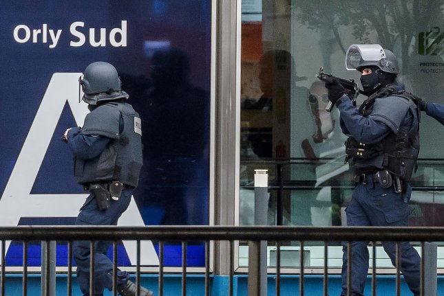 Armed police special intervention units move into position at Orly airport near Paris on Saturday. Ben Belgacem grabbed a female soldier on patrol and put a gun to her head before he was shot dead by her two colleagues. Photo by Christophe Petit Tesson/EPA