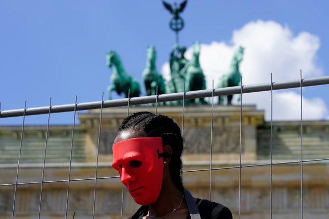 An activist of the association Together for Africa wears a masks while playing a slave during the staging of a slave market in front of Brandenburg Gate in Berlin on May 25. The group says millions of people worldwide are victims of modern slavery. Photo by EPA-EFE