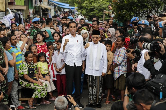 Indonesia's incumbent President from the Indonesian Democratic Party of Struggle (PDIP) Joko Widodo (C-L) and his running mate Ma'ruf Amin (C-R) pose for photographs shortly after the announcement of the election results at a slum area in Jakarta, Indonesia. Photo by Mast Irham/EPA-EFE