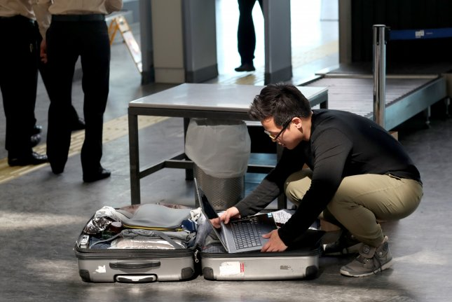 A passenger opens his luggage and shows his electronic equipment at security point at the Ataturk Airport, in Istanbul, Turkey in 2017. Counter-terrorism officials said the Islamic State has been working to build battery bombs inside laptop computer, prompting an electronics ban in carry-on luggage. Photo by Sedat Suna/EPA