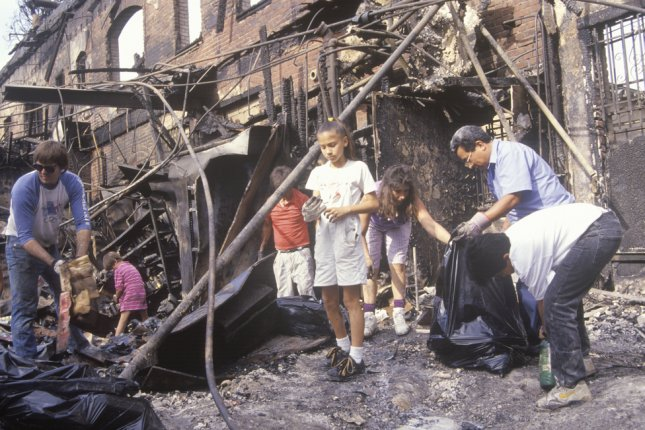 A family rummages through a home burned during the 1992 riots in South Central Los Angeles. On March 3, 1991, home video captured a Los Angeles police beating of motorist Rodney King that triggered protests and a national debate on police brutality. File Photo by American Spirit/Shutterstock.com