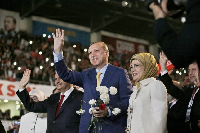 Turkish President Recep Tayyip Erdogan (C), his wife Emine (R) and Prime Minister Binali Yildirim (L) greet supporters of the ruling Justice and Development Party during an extraordinary convention on, Sunday in Ankara. Erdogan regained his party's leadership. Photo by Burhan Ozbilici/EPA