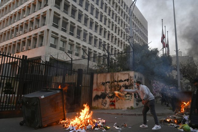 Anti-government protesters burn tires and garbage bins to block the road during a protest against the power cuts, the high cost of living and the low purchasing power of the Lebanese pound, in front of the Lebanese Central Bank at Hamra street in Beirut, Lebanon, on March 15. File Photo by Wael Hamzeh/EPA-EFE