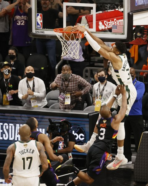 Milwaukee Bucks forward Giannis Antetokounmpo (34) dunks over Phoenix Suns guard Chris Paul (3) on an alley-oop late in the fourth quarter during Game 5 of 2021 NBA Finals on Saturday at Footprint Center in Arizona. Photo by Tannen Maury/EPA-EFE