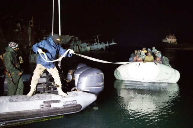 Libyan Coast Guard personnel pull a rope from an inflatable boat carrying about 120 immigrants on Feb. 4 at Tripoli bound for Italy. On Monday, the European Union's Foreign Affairs Council restricted exports of inflatable boats and outboard motors in an effort to curb the smuggling of migrants. Photo by EPA
