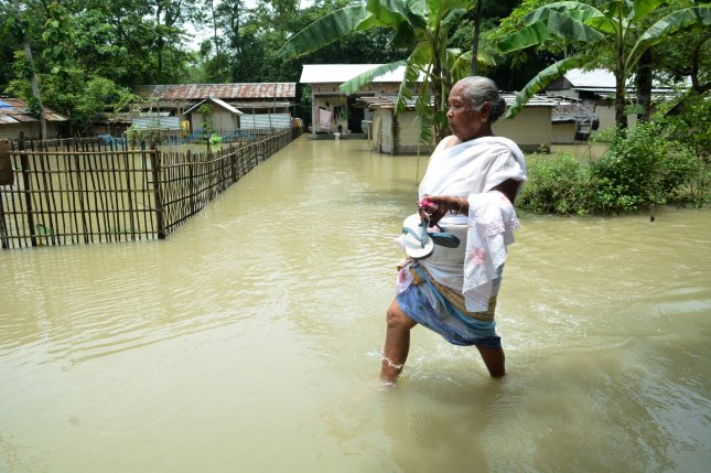 A villager wades through flood water while carrying her slippers in Salmara in the Nalbari district of Assam, India, on Sunday. Photo courtesy of Stringer/EPA-EFE