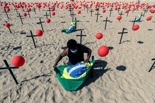 An activist ties a Brazilian national flag along with red balloons and crosses honoring victims of the coronavirus pandemic in Brazil, at Copacabana beach in Rio de Janeiro on Saturday. Photo by Antonio Lacerda/EPA-EFE