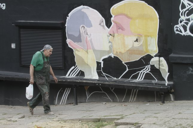 A man passes by a graffiti mural by Lithuanian artist Mindaugas Bonanu depicting then-U.S. Republican presidential candidate Donald Trump (R) kissing Russian President Vladimir Putin on the wall of a barbacue restaurant in Vilnius, Lithuania, on August 4. Photo by VALDA KALNINA/European Press Agency