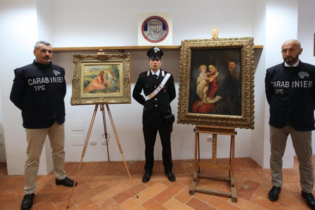 Italian carabinieri pose near the paintings Girls on the Lawn by Pierre-August Renoir (L) and Holy Family by Peter Paul Rubens (R) during a press conference in Monza, Italy, on Friday. Photo by Fabrizio Radaelli/EPA-EFE