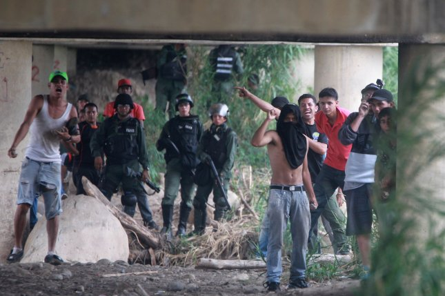 Supporters of the government of the Venezuela Nicolas Maduro and members of the Venezuelan police confront opposition protesters at the Simon Bolivar International Bridge in Cucuta, Colombia, on Saturday. The police prevented the passage of the humanitarian aid from the Colombian city of Cucuta to Venezuela through the bridge. Photo by Ernesto Guzman Jr./EPA