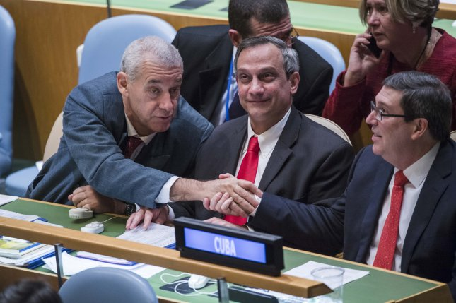 Members of the Cuban delegation congratulate Bruno Rodríguez Parrilla (right), Minister for Foreign Affairs of Cuba, following the vote to end the economic, commercial and financial embargo imposed by the United States against Cuba at the United Nations in New York on October 26, 2016. Rodolfo Reyes Rodríguez, Permanent Representative of Cuba to the United Nations, is seated at centre. Photo by Amanda Voisard/UPI