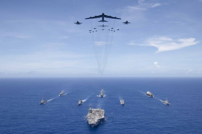 The aircraft carrier USS Ronald Reagan (CVN 76) leads a formation of Carrier Strike Group 5 ships as U.S. Air Force B-52 Stratofortress aircraft and U.S. Navy F/A-18 Hornets pass overhead for a photo exercise during Valiant Shield 2018. Photo by Erwin Miciano/U.S. Navy