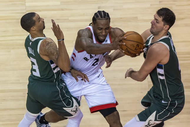 Toronto Raptors forward Kawhi Leonard (C) charges between Milwaukee Bucks guard George Hill (L) and forward Nikola Mirotic (R) in the second quarter during Game 3 of the NBA Eastern Conference Finals on Sunday at Scotiabank Arena in Toronto, Canada. Photo by Warren Toda/EPA-EFE