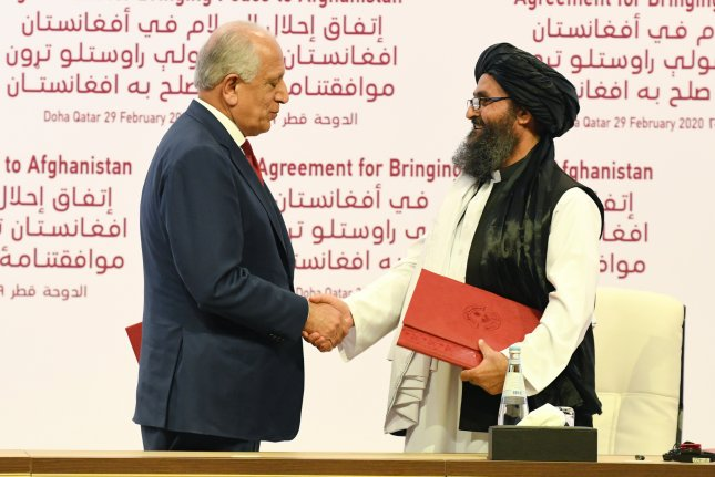U.S. Special Representative for Afghanistan Reconciliation Zalmay Khalilzad, L, and Taliban co-founder Mullah Abdul Ghani Baradar, R, shake hands during the signing ceremony of the U.S.-Taliban peace agreement in Doha, Qatar, on February 29. The first action of the peace deal, a prisoner swap of Taliban members and Afghan government forces, is expected this week. File Photo by Stringer/EPA-EFE