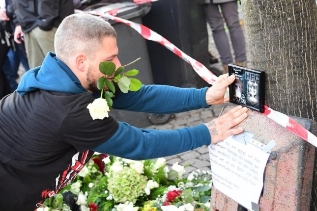A soccer fan places a commemoration picture for a victim during a visit to the Kebab snack shop that was a site of a shooting a day before in Halle, Germany. Photo by Clemens Bilan/EPA-EFE
