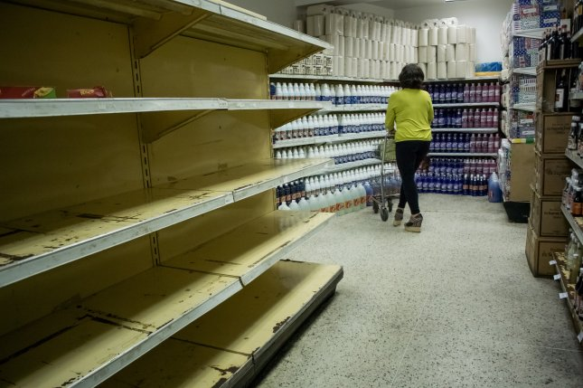 A woman shops in the cleaning supply section of a supermarket where some food supplies are no longer available in Caracas, Venezuela, on February 11, 2016. A recent survey found that nearly 75 percent of the population lost an average of at least 19 pounds in 2016 due to a lack of proper nutrition amid an economic crisis. File Photo by Miguel Gutierrez/EPA