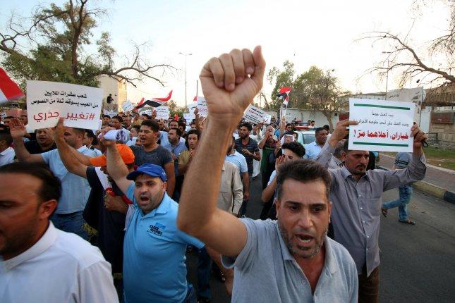 Iraqis chant slogans and carry banners during a demonstration in front of the headquarters of Basra governorate in Basra, Iraq, on Monday. Photo by Haider al-Assadee/EPA-EFE