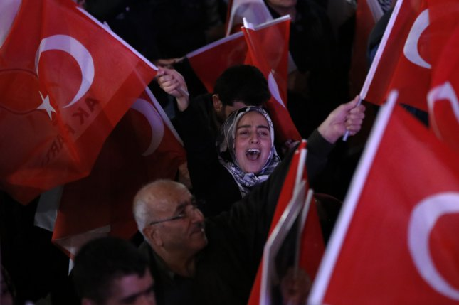 Supporters of Turkish President Erdogan celebrate his apparent victory in changing the country's parliamentary government into a presidential one, which the opposition denounced for giving too much power to Erdogan. Photo by Tumay Berkin/EPA