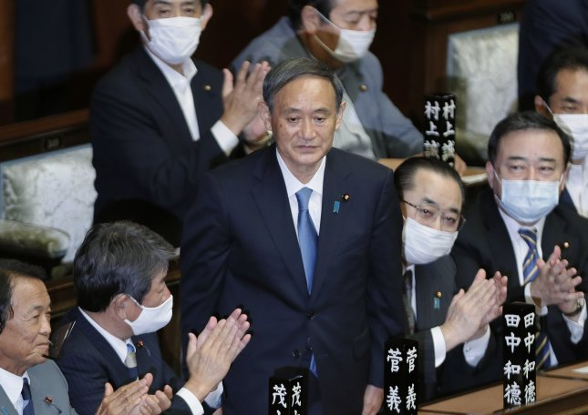 Yoshihide Suga (C) stands to applause from his colleagues after being elected Japan's prime minister at an extraordinary parliamentary session in Tokyo, Japan, on Wednesday. Suga succeeded former prime minister Shinzo Abe. Photo by Kimimasa Mayama/EPA-EFE