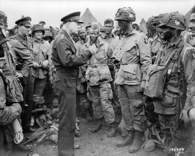 Photo shows General Eisenhower talking with American paratroopers on the evening of June 5, 1944, as they prepared for the Battle of Normandy. The men are part of Company E, 502nd Parachute Infantry Regiment, at the 101st Airborne Division's camp in Greenham Common, England. General Eisenhower gives the order of the day, Full victory--nothing else to paratroopers just before they board their airplanes to participate in the first assault in the invasion of the continent of Europe. File Photo by US Army/UPI