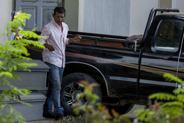Reynaldo Peralta Rodriguez leaves the morgue with the coffin of his wife, Vilma Trujillo García, who was burned in a fire in Managua, Nicaragua, on Tuesday. Pastor Juan Gregorio Rocha Romero ordered Trujillo burned at the stake, officials said. Rocha Romera and four other members of Assembly of God church were arrested. File Photo by Jorge Torres/EPA