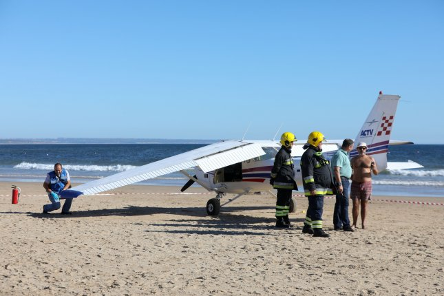 Emergency services inspect a plane that landed in an emergency on Sao Joao beach on Costa de Caparica in Almada, Portugal, on Wednesday. Two people were killed, a 50-year-old man and an 8-year-old girl after a light plane made an emergency landing on a crowded beach. The two crew members of the plane were unharmed and are interrogated by the authorities. Photo by Andre Kosters/EPA