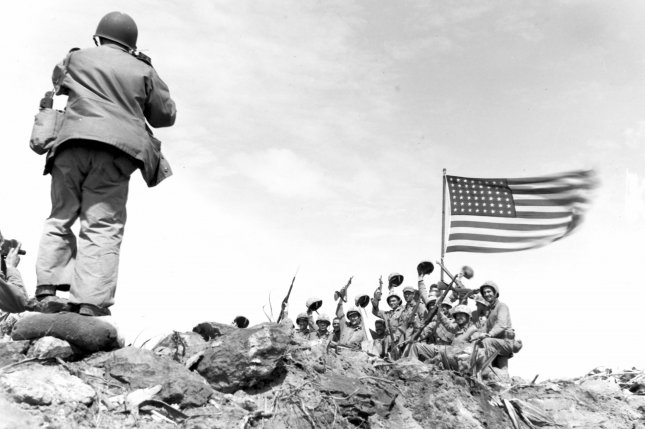 In the stiff breeze atop Iwo Jima's Mount Suribachi, Old Glory whips against the sky as members of the 5th Marine Division (United States) raise their voices and weapons in celebration, capturing the moment for posterity on February 23, 1945. File Photo by Pvt. Bob Campbell/USMC/UPI