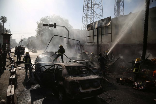 Afghan firefighters work at the scene of a suicide bomb attack in Jalalabad, Afghanistan, on July 1, 2018. File Photo by Ghulamullah Habibi/EPA-EFE