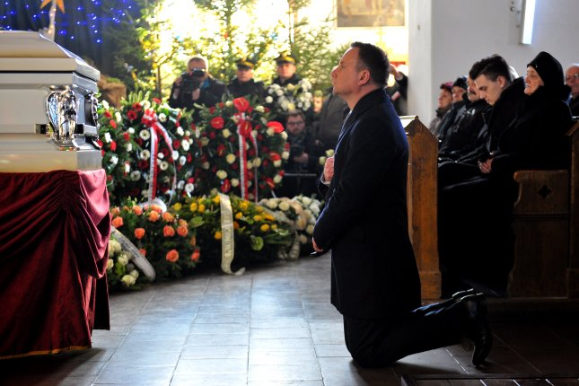 Polish President Andrzej Duda prays at the coffin of the truck driver Lukasz Urban, who was killed by a terrorist in the Berlin Christmas Market attack, during a funeral mass in Banie, Poland, on Friday. Urban was found dead in a truck used in an attack on Christmas Market in Berlin, Germany last week. Photo by Marcin Bielecki/European Pressphoto Agency