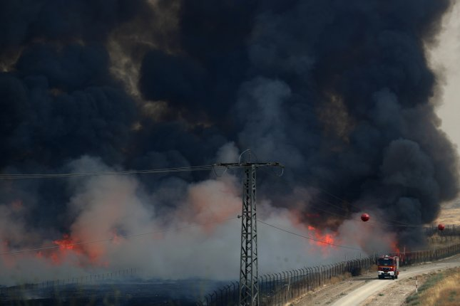 An Israeli fire crew drives on a road Friday near a blaze burning across a security fence on the Jordanian side of the border. Photo by Atef Safadi/EPA-EFE