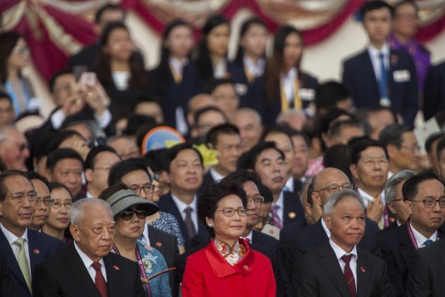 Hong Kong's new Chief Executive Carrie Lam (red dress) stands for the national anthem on July 1. File Photo by Alex Hofford/EPA
