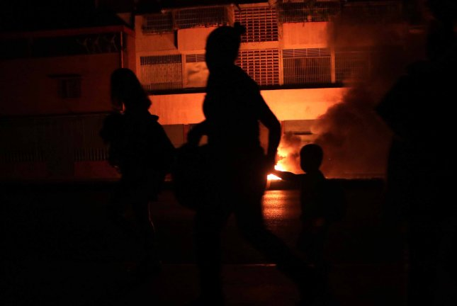 People walk in a street in the dark during a power outage in Caracas, Venezuela, that embattled President Nicolas Maduro has blamed on a cyber attack launched by the United States. Photo by Rayner Pena/EPA-EFE