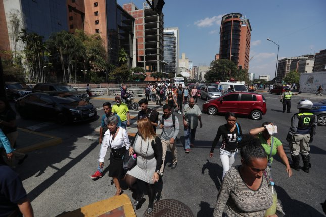Dozens of people move on foot and wait for buses due to the suspension of Metro service due to a blackout in Caracas, Venezuela, on Tuesday that started Monday night. Photo by Rayner Pena/EPA-EFE
