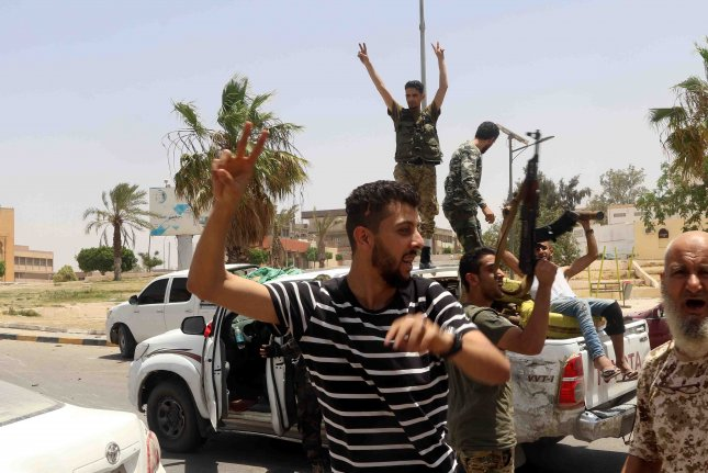 Fighters loyal to the United Nations-recognized Libyan Government of National Accord pose for a photo after the area was taken over by GNA-aligned forces following clashes with rival troops loyal to rebel leader Khalifa Haftar amid the ongoing Second Libyan Civil War in the town of Tarhuna. Photo courtesy of Stringer/EPA-EFE