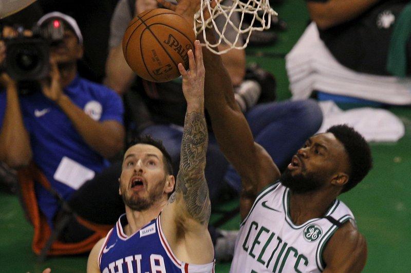 Boston Celtics guard Jaylen Brown (R) blocks the shot of Philadelphia 76ers guard JJ Redick (L). Photo by C.J. Gunther/EPA-EFE