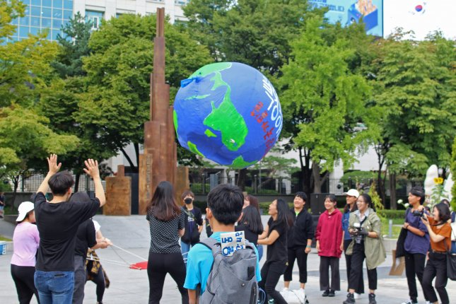 Students bounce an inflatable earth ball near Gwanghwamun Square at a rally against climate change on Friday in Seoul. Photo by Kelly Kasulis/UPI