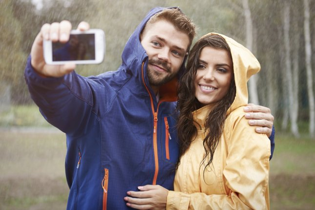 A couple snap a selfie in rainy weather. The British Environment Agency and the Society for the Prevention of Accidents are calling on residents to resist the temptation to take dangerous storm selfies in Storm Barney. Photo by gpointstudio/Shutterstock.com